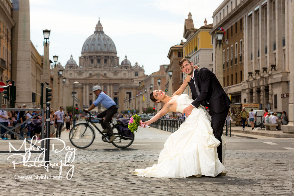 wedding photography in Rome outside the vatican, groom dips bride with bouquet as cyclist passes in background, rome destination wedding photography