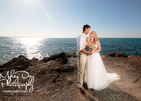 Crete wedding photo of bride and groom against the blue sky on rocky beach in Greece, destination wedding photography at the Stella Palace Hotel