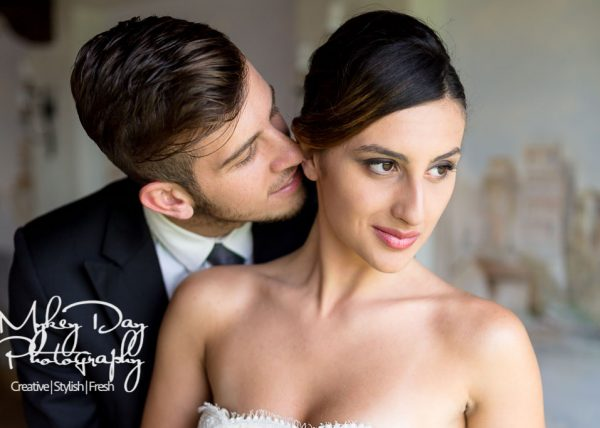 groom kissing brides ear on wedding day at Roman villa in Italy, stunning bridal portrait