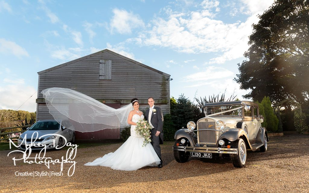Dover wedding photography, flowing veil in the wind of couple by wedding car Rolls Royce in front of Reach Court Barn wedding venue, blue skies and large bouquet