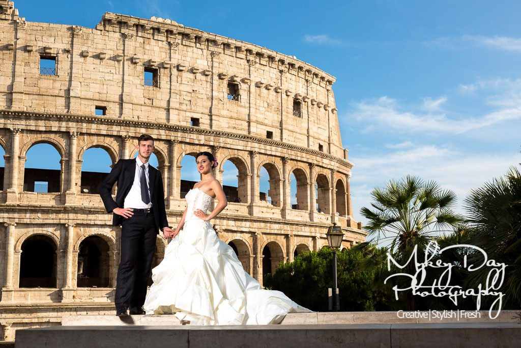 bride and groom stunning wedding photo by colosseum in Rome, long flowing white dress and groom in suit