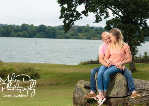 Kent wedding photographer engagement photography session for valentines day, couple sitting on log by lake, arms around waist