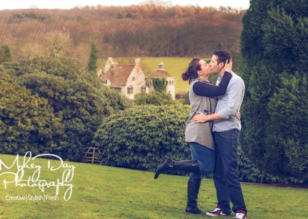 fiancee kisses boyfriend and raises leg at Scotney Castle in South-East England during pre-wedding session