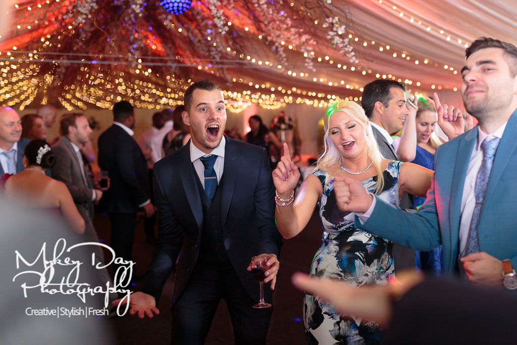 wedding guests dancing on dance floor, man in suit singing, fairy lights in marquee, kent wedding photography
