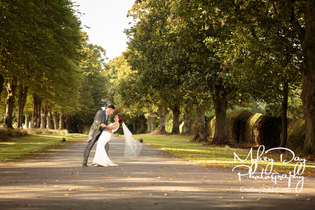 The groom dips the bride in green tree driveway at Knowlton Court wedding venue