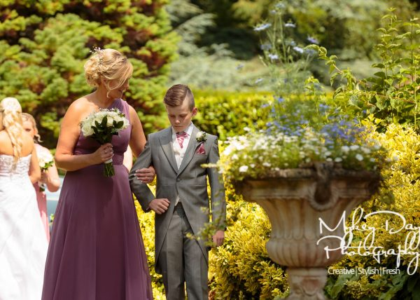 bridesmaid holding page boys arm with wedding flowers at St. Clere's Estate wedding venue, nervous boy at wedding