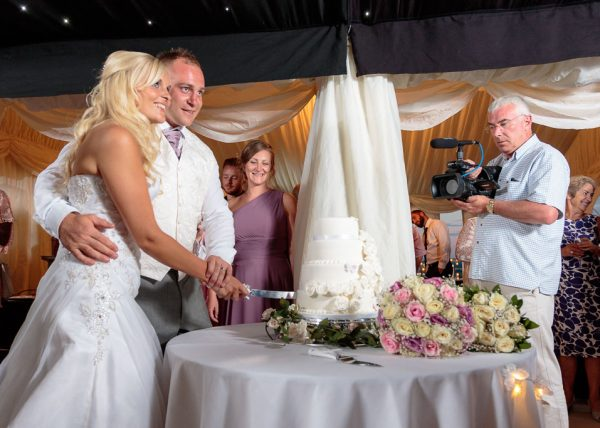 kent wedding cake, bride and groom cutting cake as videographer watches